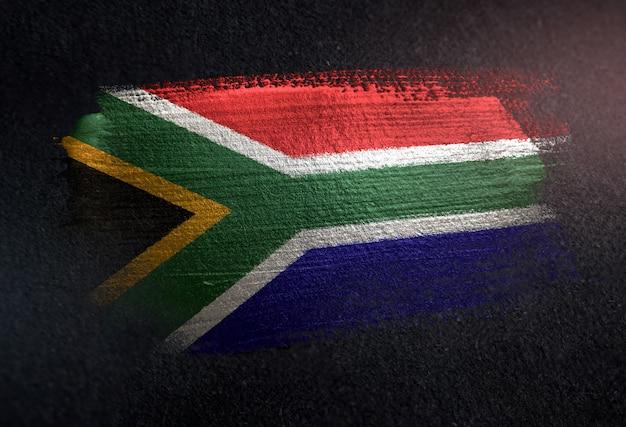 Südafrika-flagge gemacht von der metallischen bürsten-farbe auf dunkler wand des schmutzes
