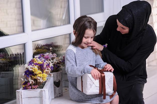 Südostasiatisches mädchen mit geschenkbox. lebensstil der muslimischen familie. glücklich lächelnde malaiische eltern und kind.