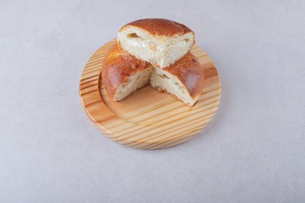 Süß geschnittenes brötchen auf holzplatte, auf dem marmor.