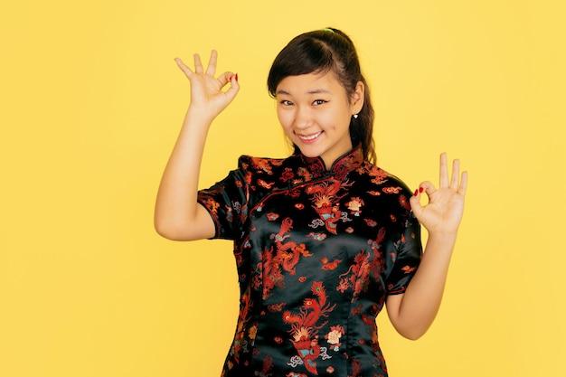 Süß lächelnd, nett zeigend. frohes chinesisches neujahr. asiatisches junges mädchenporträt auf gelbem hintergrund. weibliches modell in traditioneller kleidung sieht glücklich aus. feier, menschliche gefühle. copyspace.