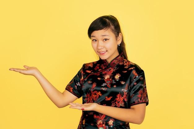 Süß lächelnd, seitlich zeigend. frohes chinesisches neues jahr 2020. porträt des asiatischen jungen mädchens auf gelbem hintergrund. weibliches modell in traditioneller kleidung sieht glücklich aus. feier, menschliche gefühle. copyspace.