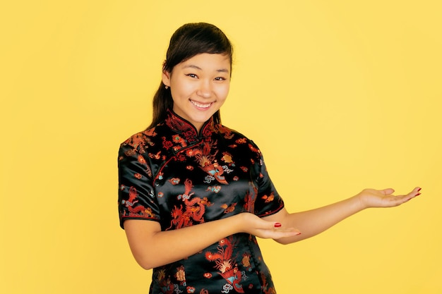 Süß lächelnd, seitlich zeigend. frohes chinesisches neujahr. asiatisches junges mädchenporträt auf gelbem hintergrund. weibliches modell in traditioneller kleidung sieht glücklich aus. feier, menschliche gefühle. copyspace.