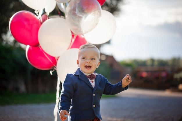 Süß verspielt lächelte blond. 1 jahre alte junge, die auf grünem gras outdor spielt mit ballon sitzen.