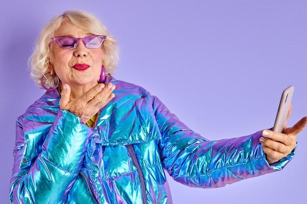 Süße ältere dame blasen kuss an der kamera des smartphones, posiert, spricht online mit jemandem