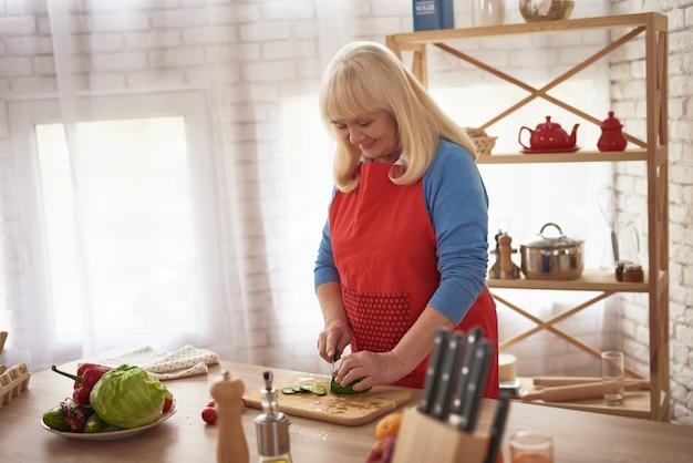 Süße alte dame cooking zu hause, die gemüse schneidet.