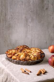 Süße apfelklebrige zimtschnecken in rundem backblech stehen mit gartenäpfeln und zimtstangen auf grauer leinentischdecke. traditionelle hausbäckerei, textfreiraum