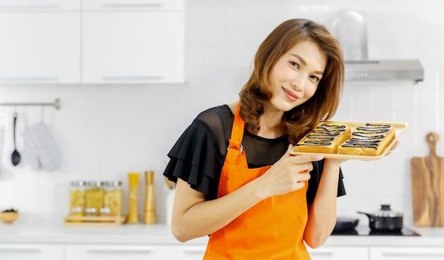 Süße asiatische frau mit orangefarbener schürze, die von kochgeräten umgeben ist, lächelt und zeigt ein tablett mit leckerem brot mit dunkler schokoladencreme.
