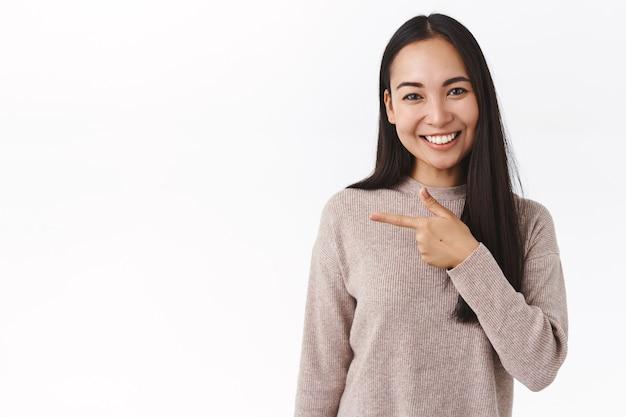 Süße asiatische freundin gibt ratschläge, wo man für den urlaub einkauft, einen link oder eine anwendung empfiehlt, nach links zeigt und fröhlich lächelt, freundlich über weißer wand steht und beiläufige diskussionen führt