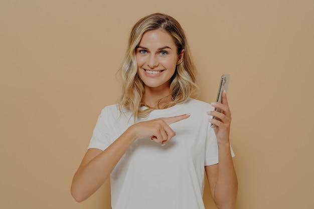 Süße aufgeregte frau, die mit dem zeigefinger auf das smartphone zeigt und mit breitem lächeln in die kamera schaut, gute nachrichten im internet liest und sich glücklich fühlt, während sie einzeln auf beigem hintergrund posiert