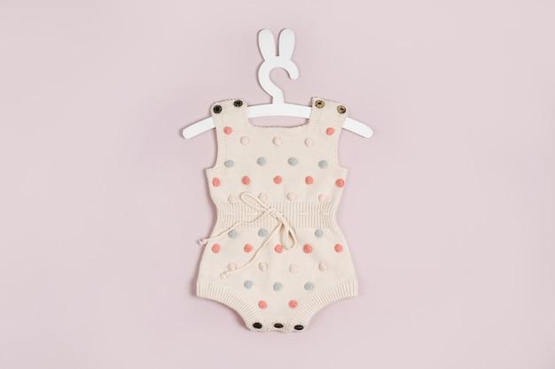 Süße babykleidung und accessoires auf rosa hintergrund. gestrickter strampler in pastellfarben
