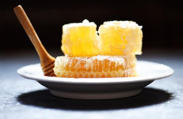 Süße bienenwabenscheibe des neuen honiggesunden lebensmittelgelbs mit hölzernem schöpflöffel auf weißer platte