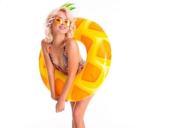 Süße blonde dame in einem badeanzug mit schwimmender kreisananas auf weiß