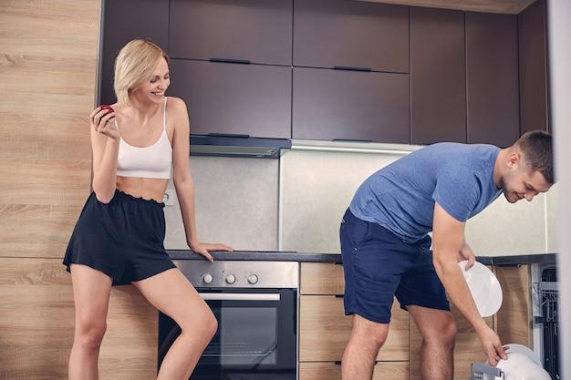 Süße blonde dame in freizeitkleidung, die roten apfel isst, während brünette männer geschirr in die spülmaschine stellen putting