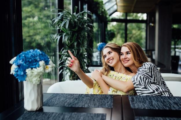 Süße, blonde junge tochter umarmt ihre mutter mit liebe auf der sommerterrasse im restaurant
