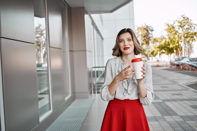 Süße blonde tasse kaffee im freien in der nähe der gebäudemode
