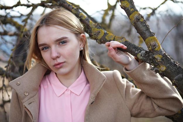 Süße blondine in einem stadtpark an einem kalten sonnigen tag