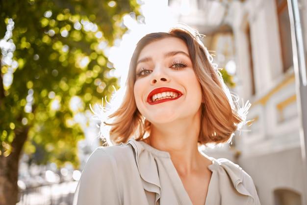 Süße blondine mit roten lippen lächelt im freien spaß