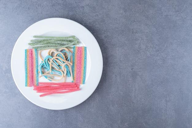 Süße bonbons auf der holzplatte auf dem marmortisch.