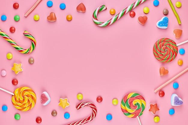 Süße bonbons und lutscher auf rosa hintergrund