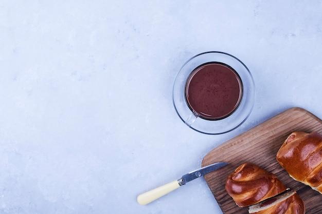 Süße brötchen auf einem holzbrett mit einer tasse heißer schokolade in der unteren ecke