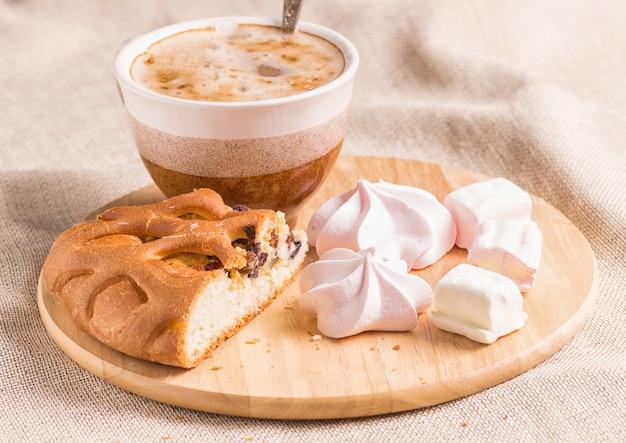 Süße brötchen, meringen und kaffeetasse auf einem hölzernen brett