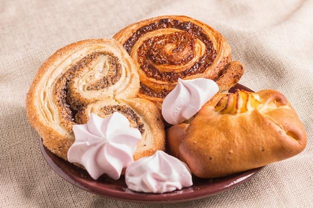 Süße brötchen und meringues auf einem holzbrett