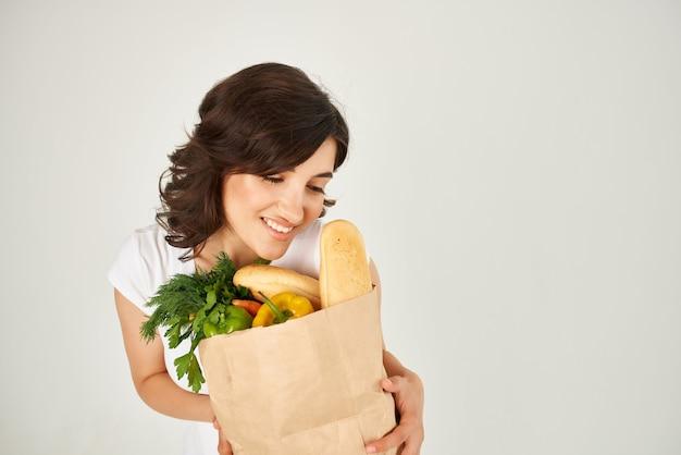 Süße brünette im weißen t-shirt übergibt paket mit supermarktlebensmitteln