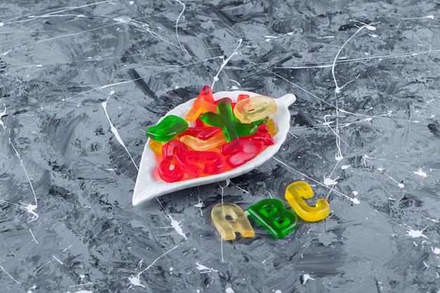 Süße buchstaben formten marmeladen auf einer marmoroberfläche.