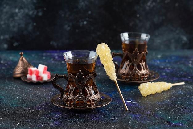 Süße bunte bonbons und duftender tee auf blauer oberfläche