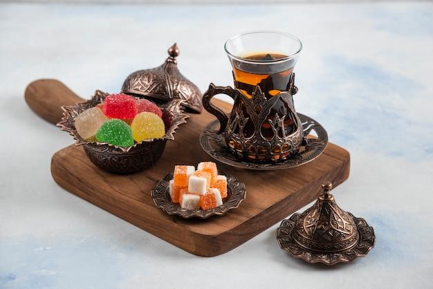 Süße bunte bonbons und duftender tee auf holzbrett