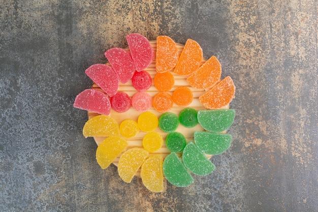 Süße bunte geleebonbons auf holzteller