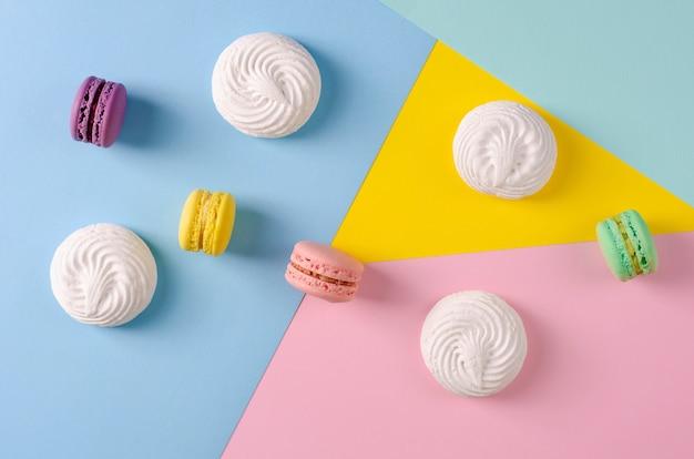 Süße bunte makronen oder macarons auf bunten pastellfarben