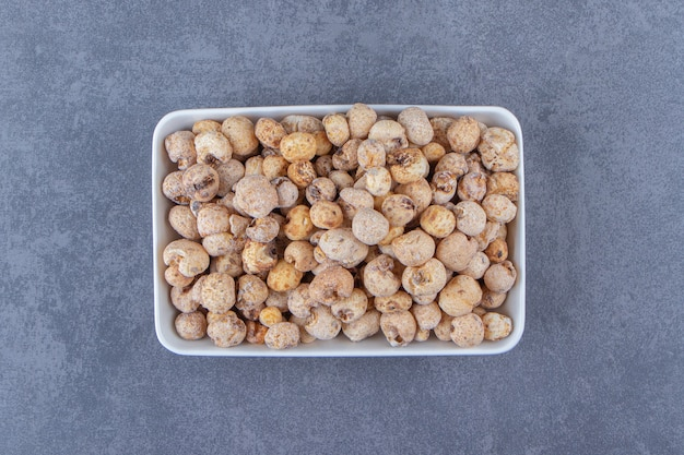 Süße cornflakes mit müsli in einer schüssel auf dem marmorhintergrund. foto in hoher qualität