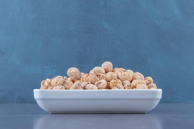 Süße cornflakes mit müsli in einer schüssel auf dem marmorhintergrund.