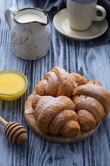 Süße croissants, honig und kaffee