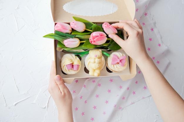 Süße cupcakes und rosa blumen in einer schachtel mit frauenhänden