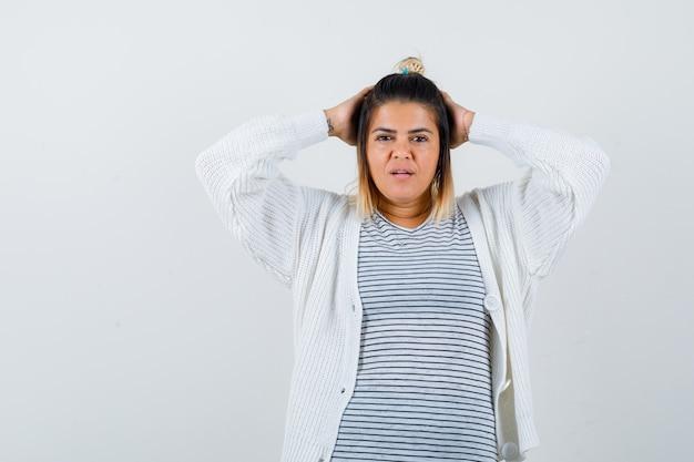 Süße dame, die die hände hinter dem kopf in t-shirt, strickjacke hält und verwirrt aussieht. vorderansicht.