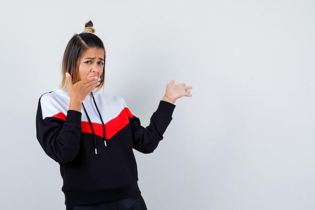 Süße dame, die die hand auf dem mund hält, die handfläche im hoodie zur seite ausbreitet und überrascht aussieht. vorderansicht.