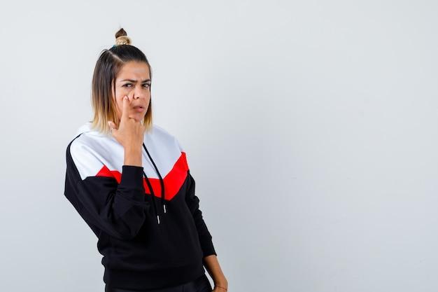Süße dame, die im hoodie auf ihr augenlid zeigt und traurig aussieht, vorderansicht.