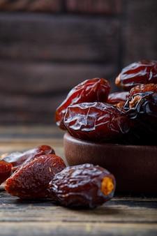 Süße datteln in einer tonplatte auf steinfliese und hölzernem hintergrund, nahaufnahme.