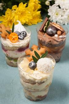 Süße desserts in plastikbechern mit sahne und schokolade