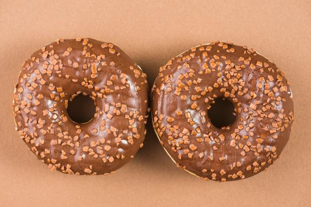 Süße donuts, die mit glasiert werden, besprüht auf braunem hintergrund