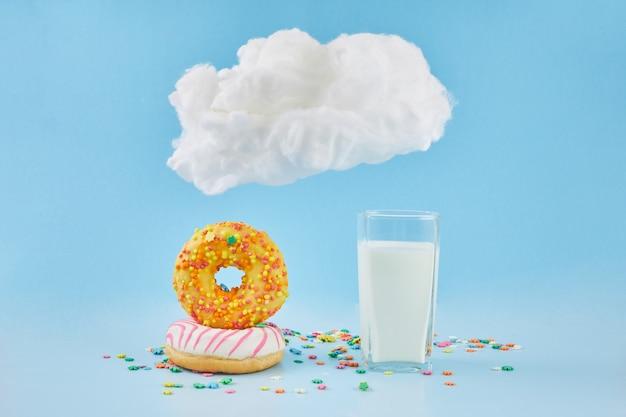 Süße donuts mit sprinkel und milch unter einer kleinen wolke auf einem rosa hintergrund. verschiedene dekorierte donuts als konzept für ein frisches leckeres frühstück.