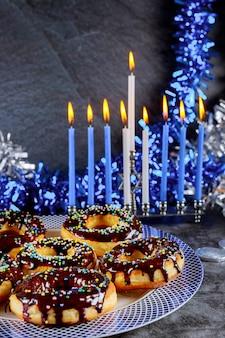 Süße donuts und menora mit brennenden kerzen