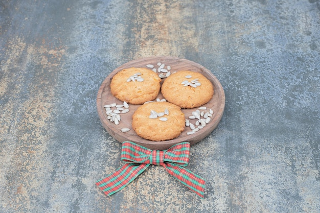 Süße drei kekse mit schöner schleife auf holzbrett.