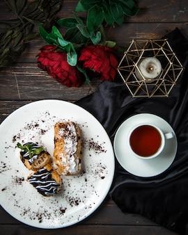 Süße eclairs mit draufsicht des schwarzen tees