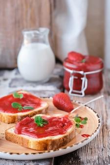 Süße erdbeermarmelade auf toastnahaufnahme. selektiver fokus. der snack ist mit minzblättern, vertikalem rahmen und nahaufnahme dekoriert. idee für frühstück oder mittagessen