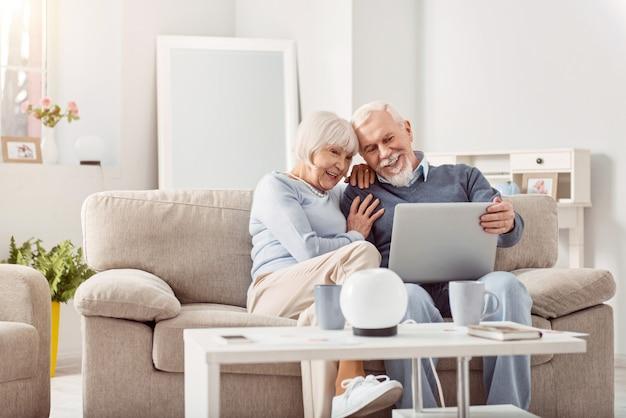 Süße erinnerungen. glückliches älteres paar, das auf der couch sitzt und kuschelt, während es durch die fotos ihrer enkelkinder auf laptop schaut