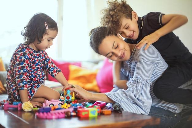 Süße familie, die mit spielwaren im wohnzimmer spielt
