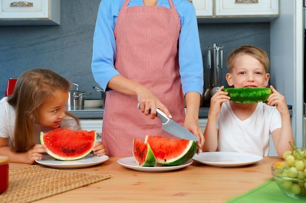 Süße familie, mutter und ihre kinder essen wassermelone in ihrer küche und haben spaß